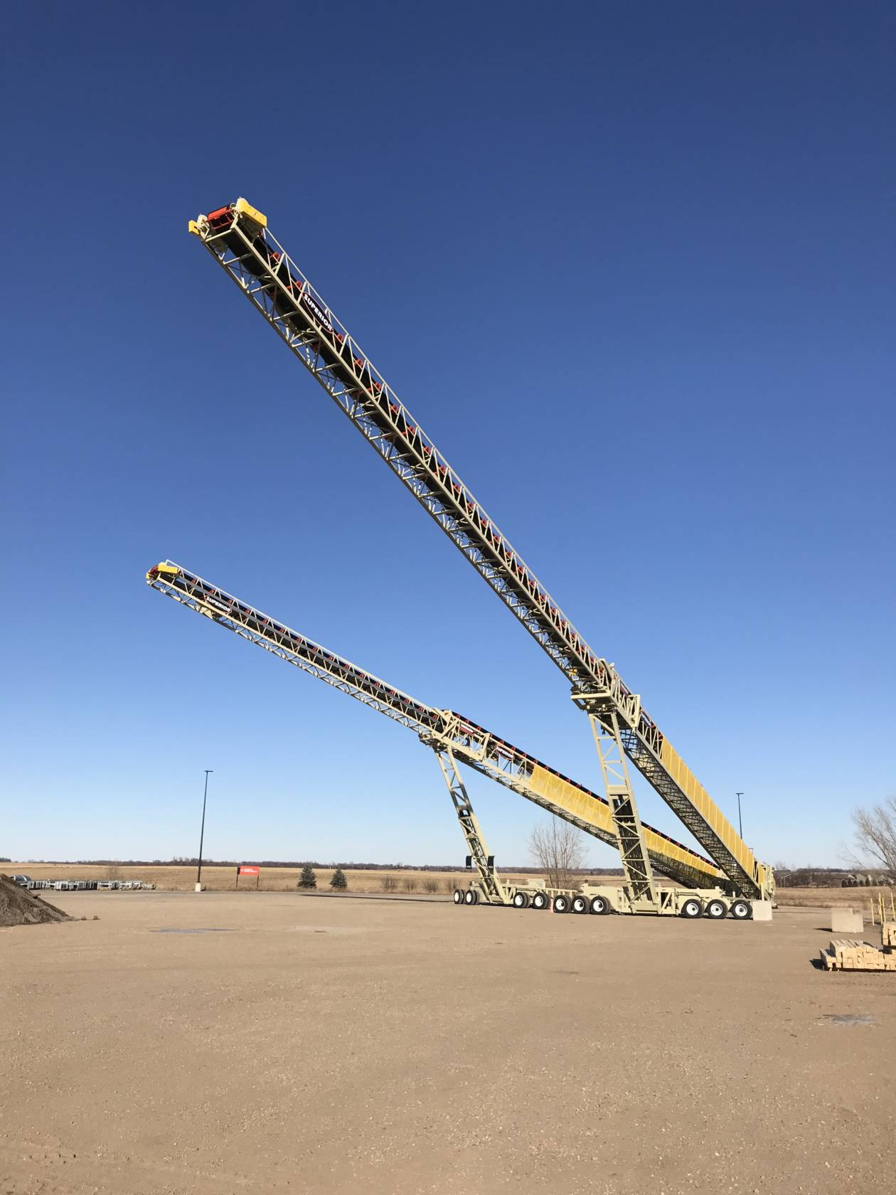 The 210′ (64m) long TeleStacker® Conveyor is shown next to a shorter model…a 170′ (52m).