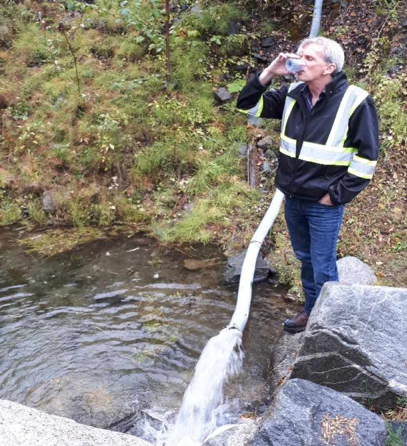 CEO Chris Anderson drinking water from the Kenville mine discharge