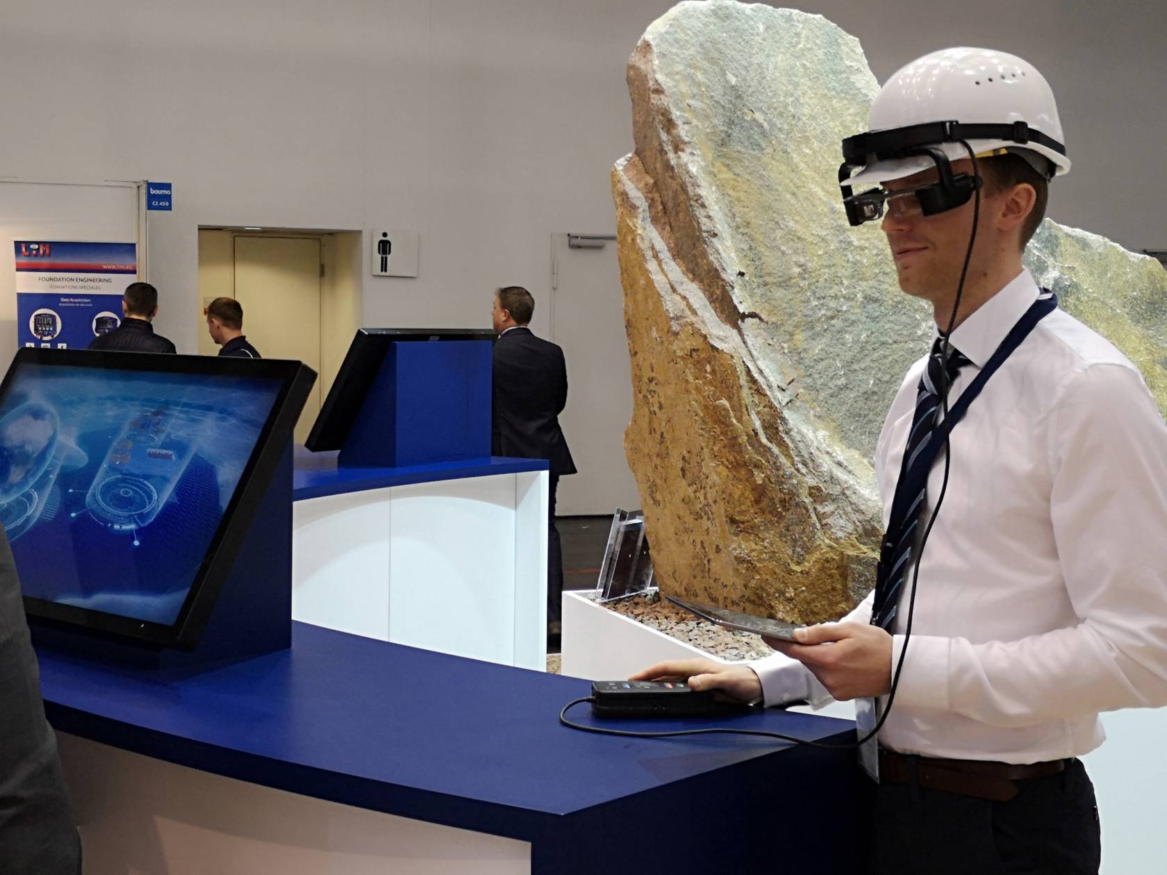 """This picture shows the use of TAKRAFs remote support application – """"smart glasses"""". By using this tool, experts in an office environment can connect to commissioning or maintenance staff on site to solve specific problems. This system was demonstrated at the 2019 BAUMA exhibition in Munich (Germany) and attracted a lot of interest from a variety of visitors."""
